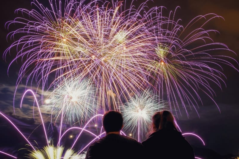 man and woman watching fireworks at night