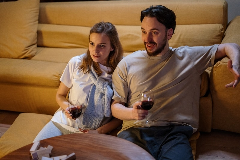 man and woman watching movie while holding glasses of wine