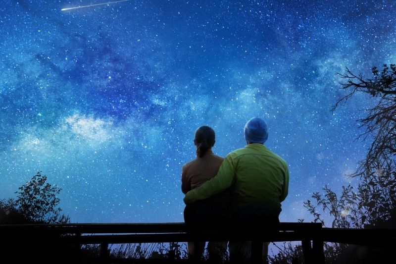 couple waching the stars during nightime sitting on a bench outdoors