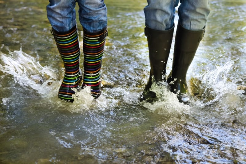 happy couple wearing colorful rain boots