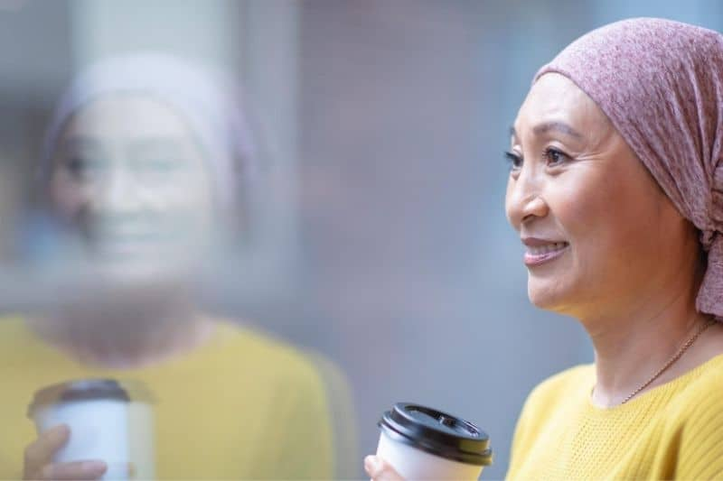 courageous korean woman having cancer holding a cup of coffee standing near a glass wall