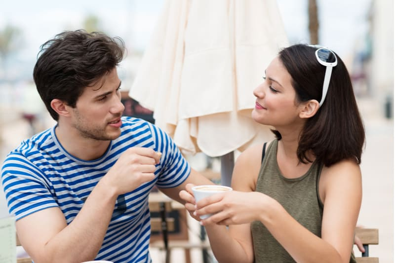 cute pretty couple talking while drinking coffee outdoors
