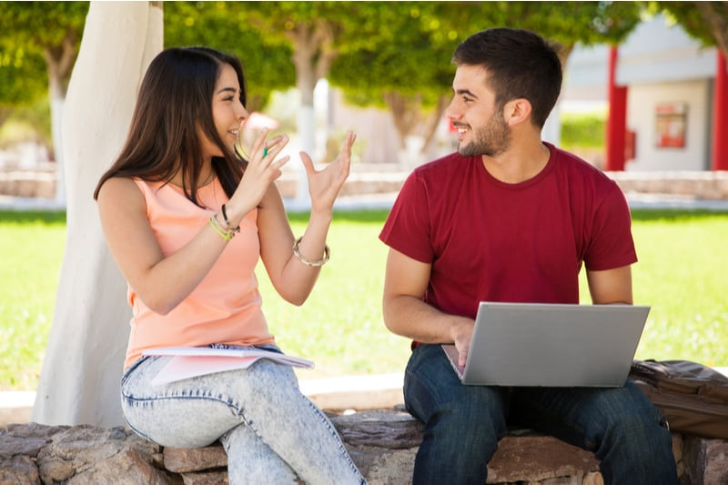 cute woman talking with man doing something on laptop sitting on the bench outdoors