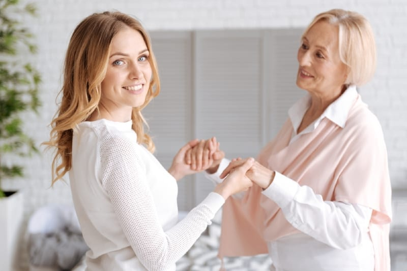 smiling daughter in white top holding mother's hands