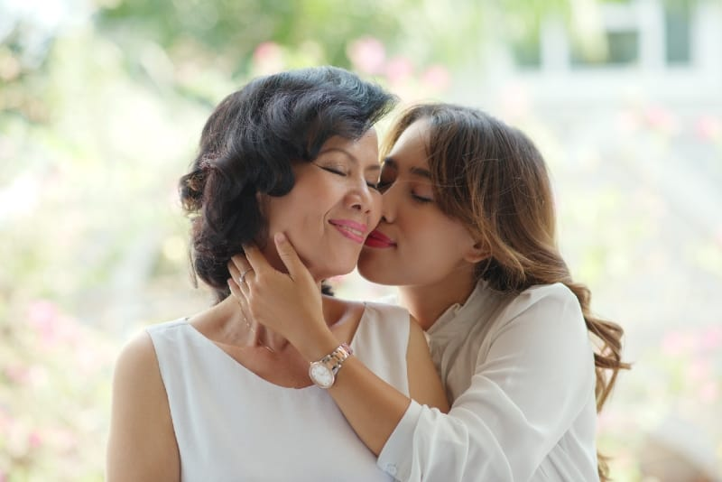 daughter in white blouse kissing mother
