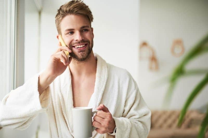 delighted young man talking on the mobile phone while holding a cup of coffee in the morning