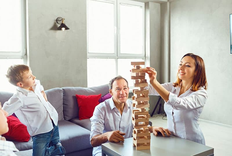 family playing jenga block inside living room with womans turn to play