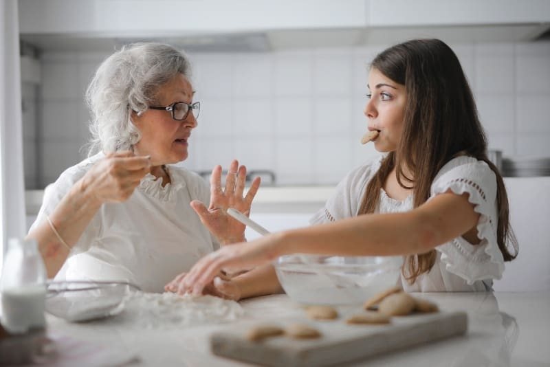 grandmother talking to granddaughter while sitting at table