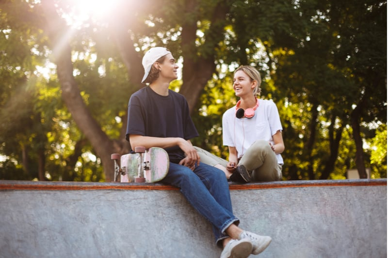 guy with a skateboard sitting next to a woman with headphones