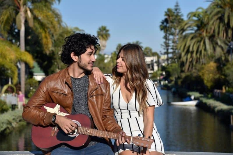 handsome man playing guitar with a woman smiling and sitting near the river bank
