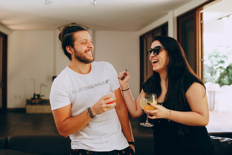 happy couple drinking cocktails inside home