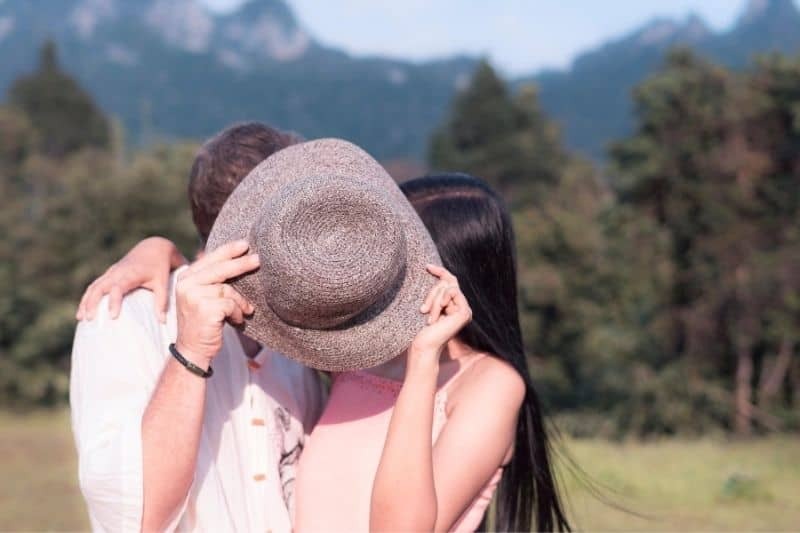 happy couple kissing outdoors covering their face with a hat