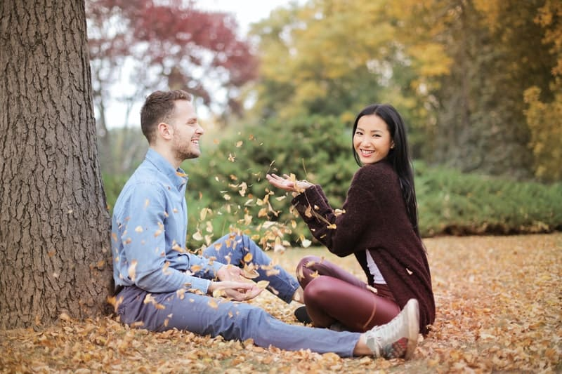 happy couple scattering dried leaves in the park while sitting on the ground