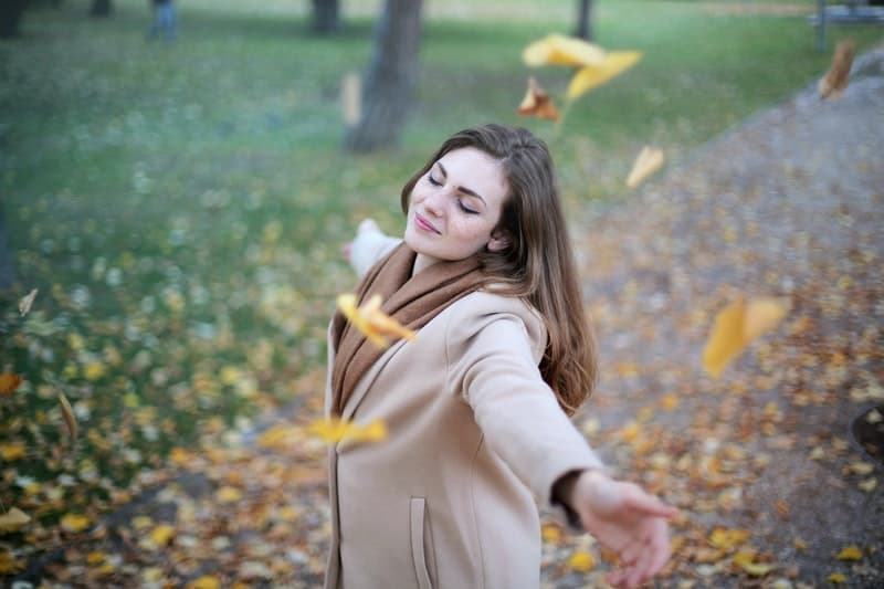 happy woman circling around with falling dried leaves and closing her eyes