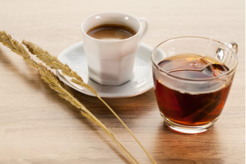 hot tea and coffee on wooden table with plant