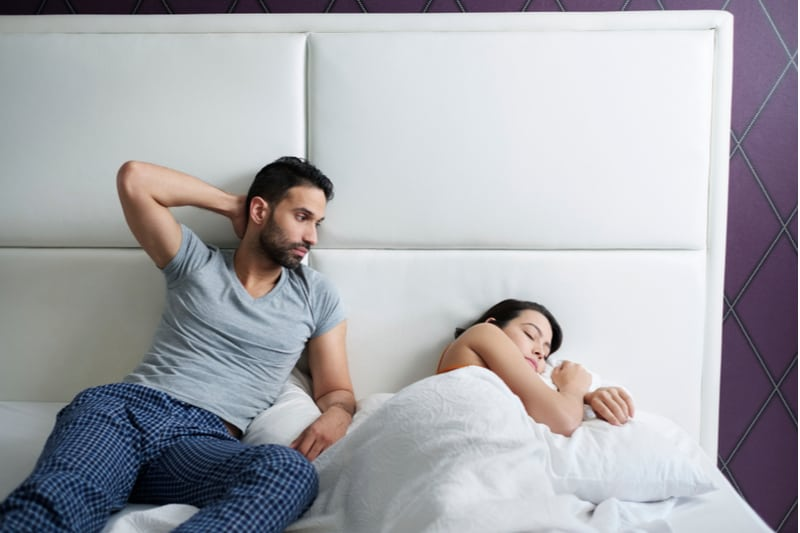 husband trying sexual approach to the bored wife in bed