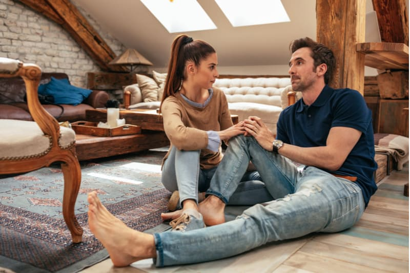 image of a couple talking inside the attic room of the house holding hands