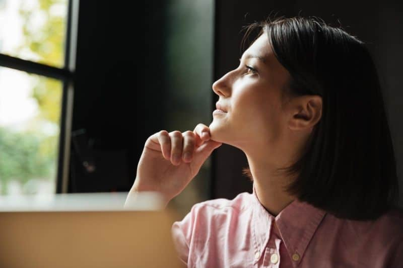 image of a pensive woman sitting inside a cafe with a laptop on the table