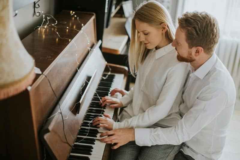 loving couple playing piano where woman sits on man's lap