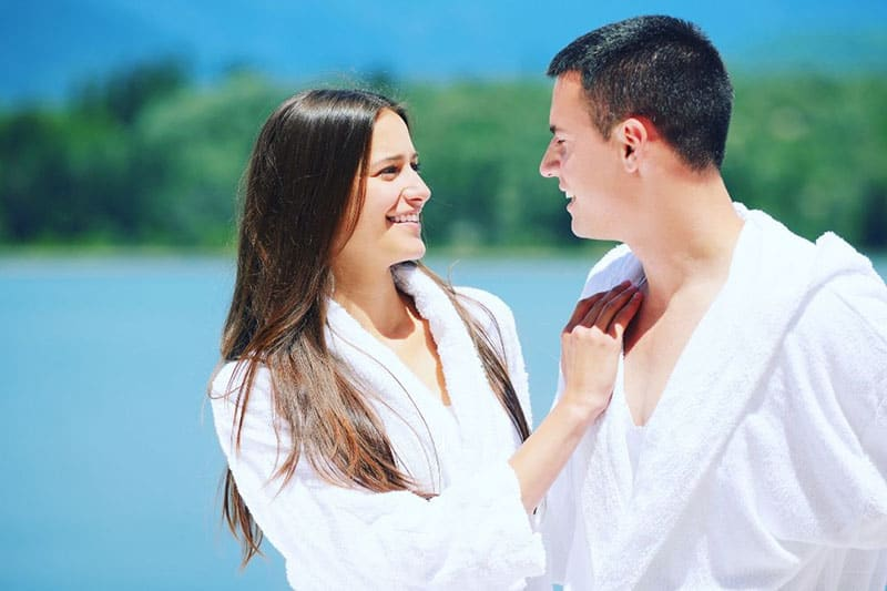 man and woman in white robe standing near the body of water