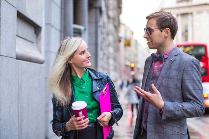man and woman talking in the street woman bring coffee