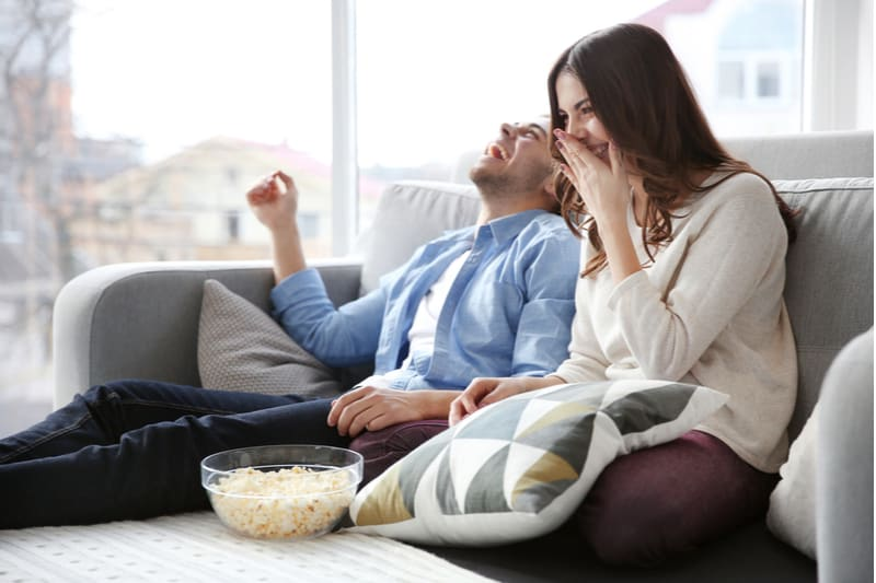 man and woman watching tv on the couch laughing and eating popcorn
