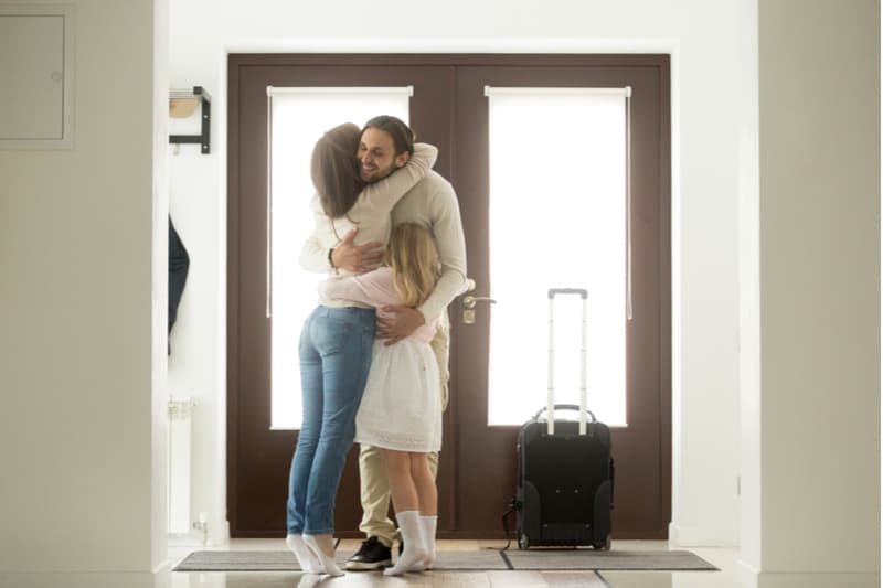 man coming home embraced and greeted by family near the door