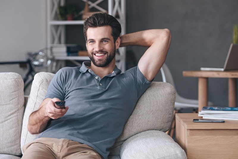 smiling man holding remote control while sitting on sofa