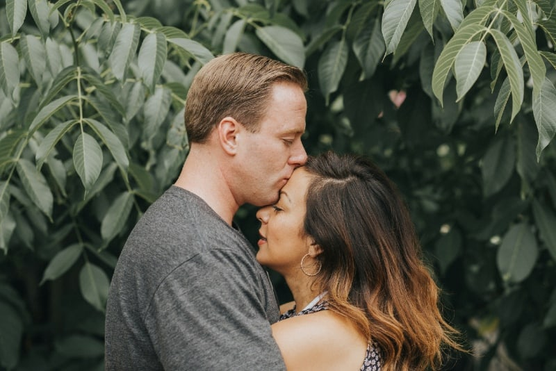 man kissing woman's forehead near tree