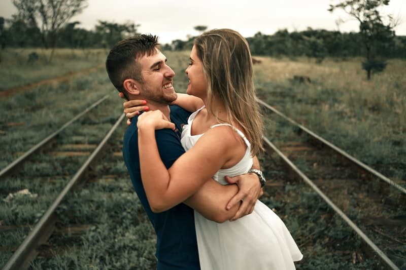 man lifting woman in the middle of the railway track