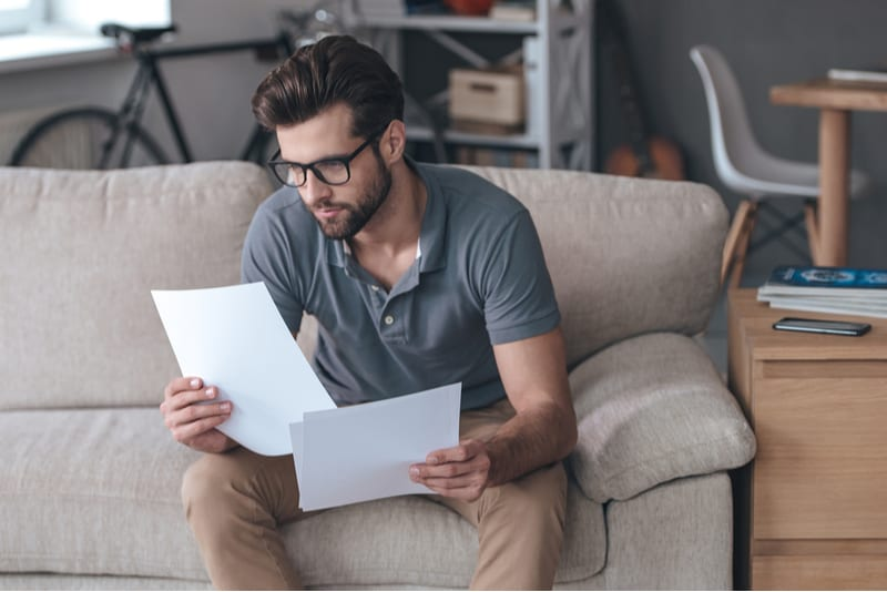 man looking at papers inside home sitting on sofa