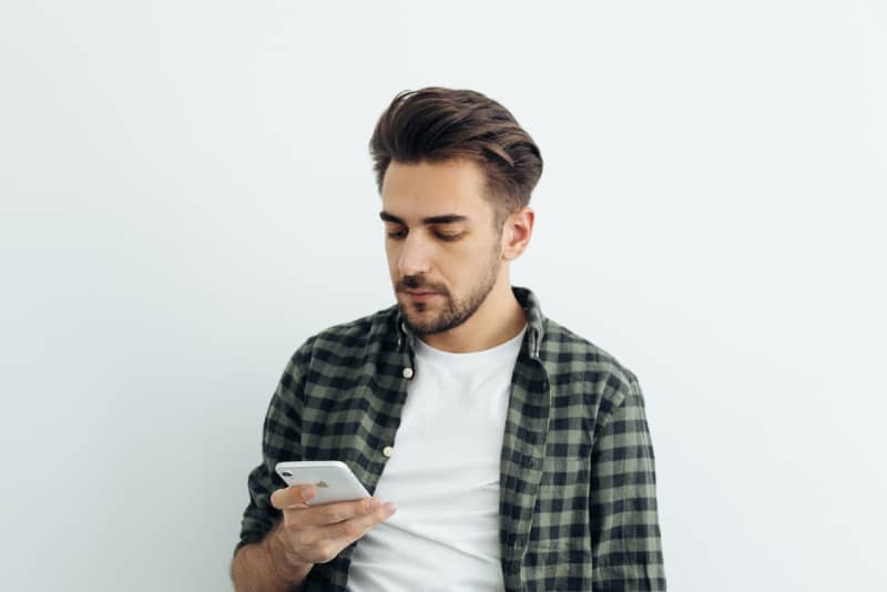 man looking at phone while standing near white wall