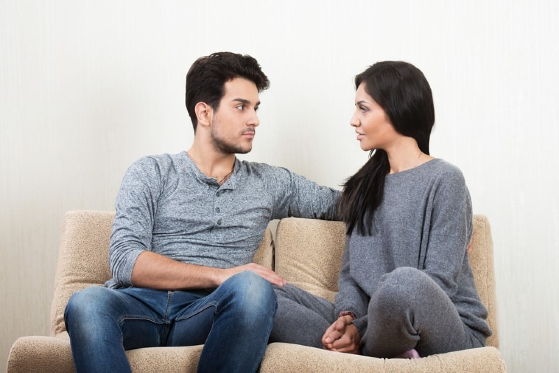man looking at woman while sitting on sofa