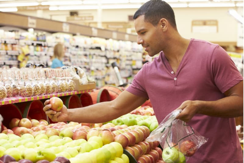 man picking groceries choosing fruits in the fruit section