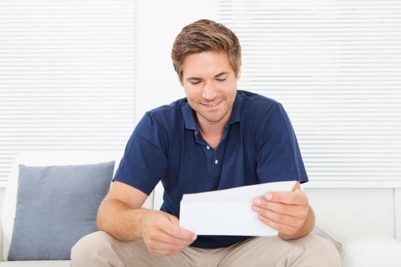 man reading a letter smiling and sitting in the couch smiling