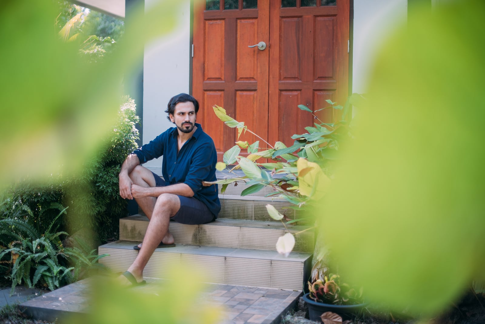 man sits on the porch of a house