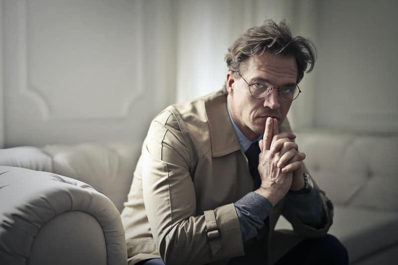 man sitting on sofa thinking deeply inside living room