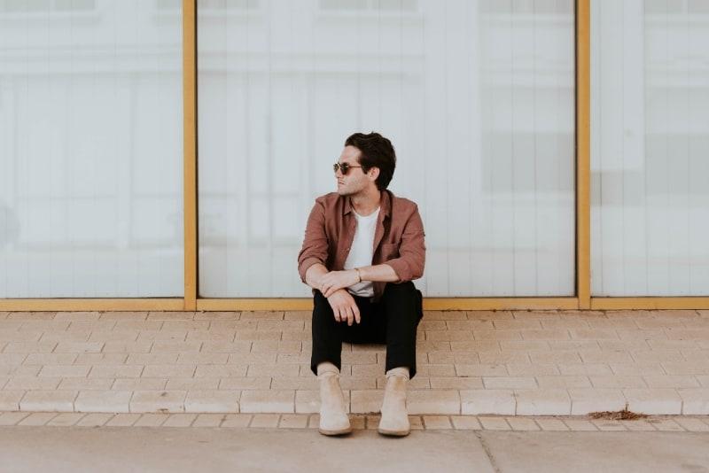 man with sunglasses sitting on window ledge