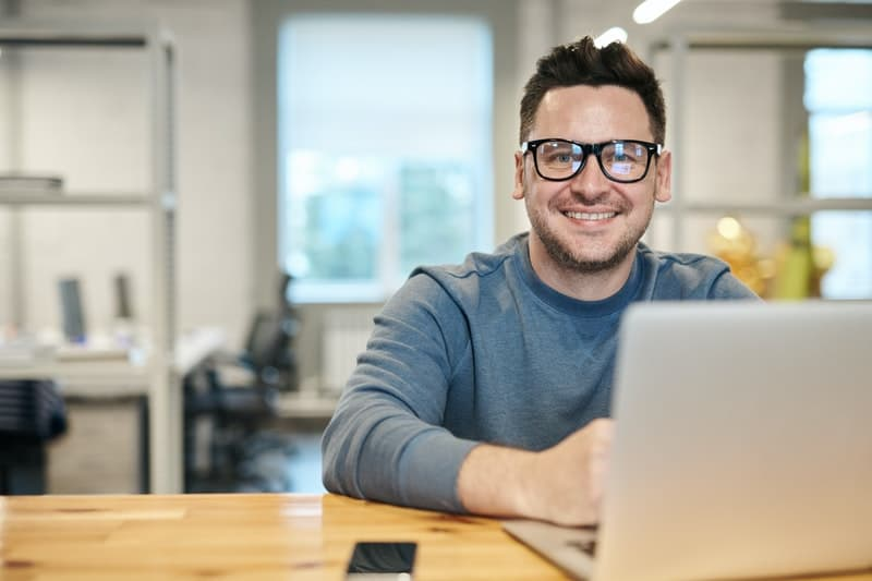 man smiling looking at the camera sitting in his desk inside office