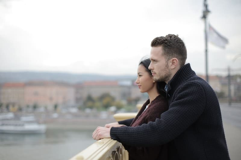 man standing at the back of the woman while leaning on the ledge of a bridge