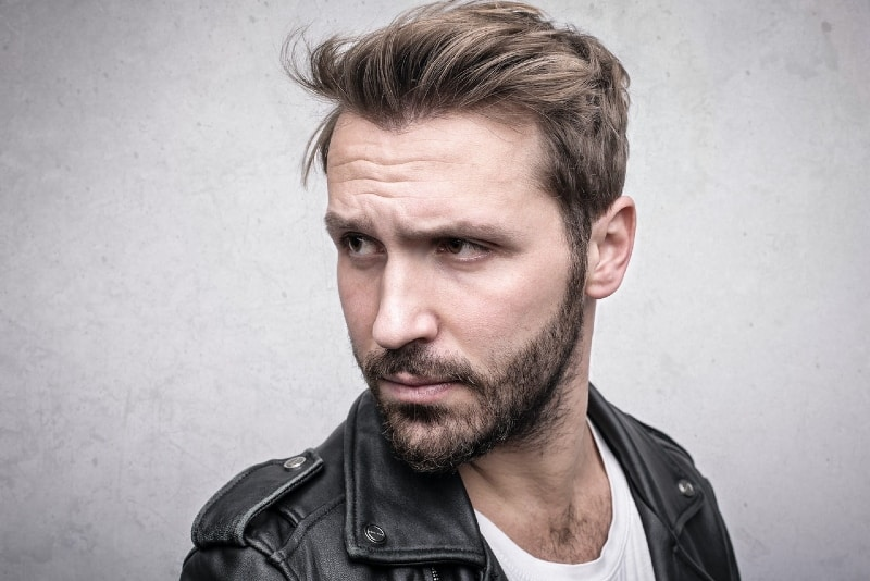 man in black leather jacket standing near wall