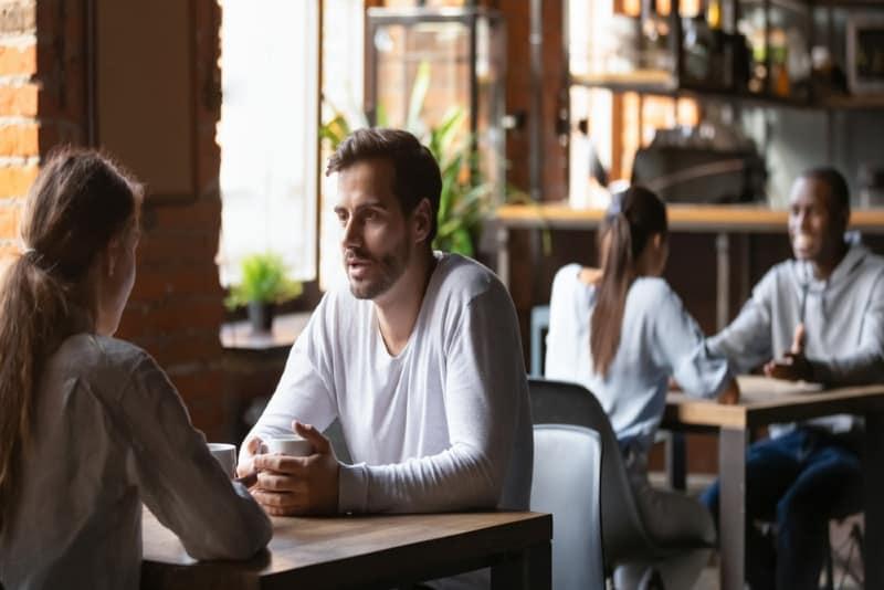 man in white shirt talking to woman