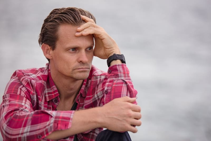 man in red checked shirt touching his forehead