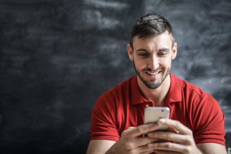smiling man in red t-shirt using smartphone