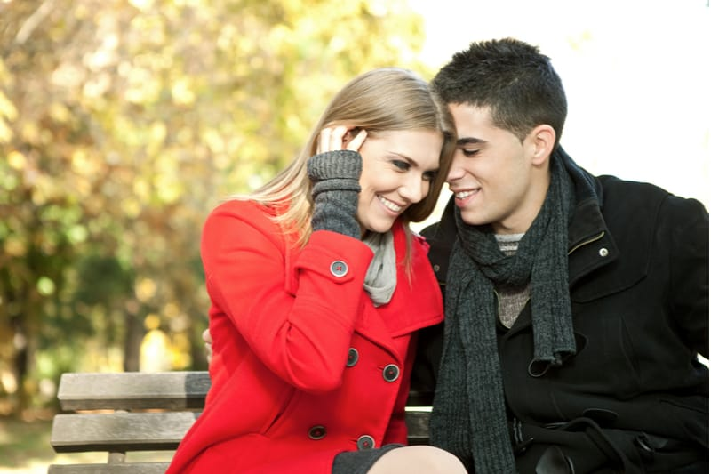 man whispering something to the woman sitting on the bench outdoors