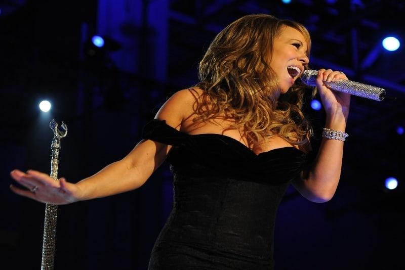 mariah carey in black dress holding a microphone
