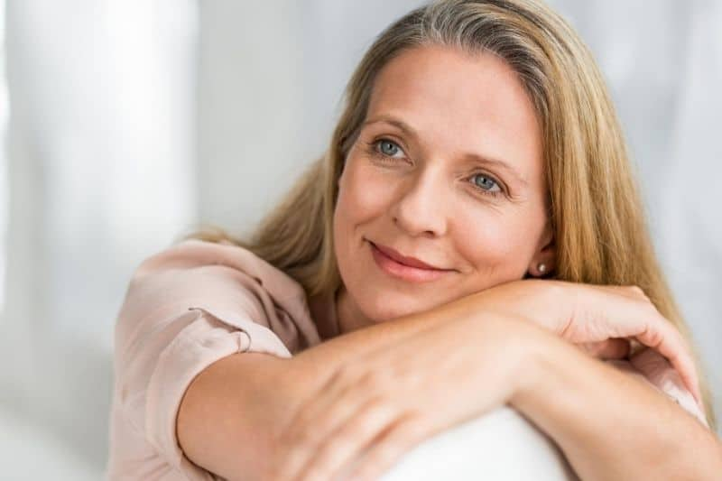 mature woman thinking and smiling while resting on couch