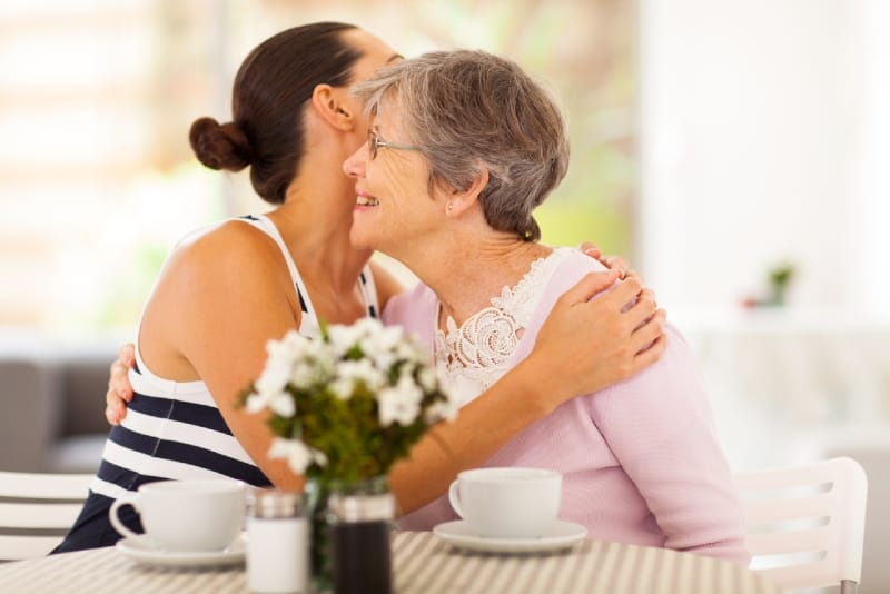 mother and daughter hugging while sitting at table