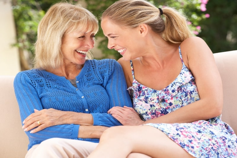 smiling mother in blue top and daughter sitting on sofa