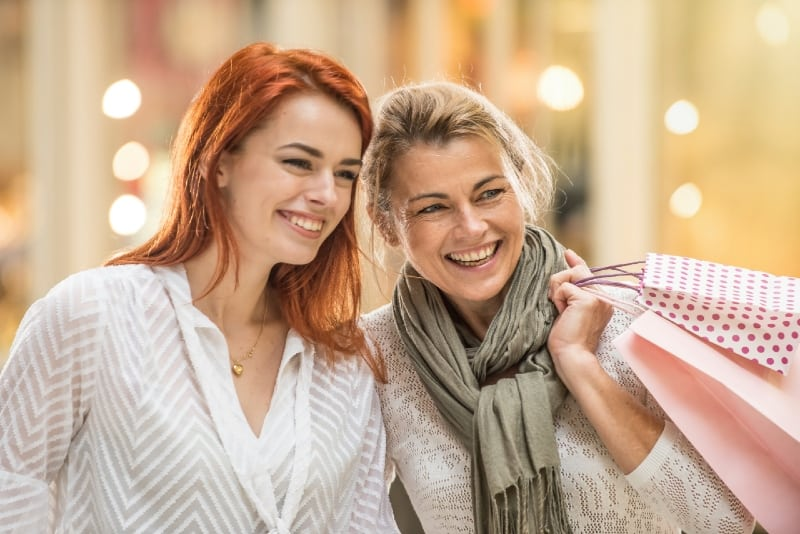 mother with paper bags and daughter smiling